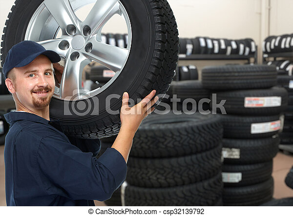 Car mechanic with a tire. - csp32139792