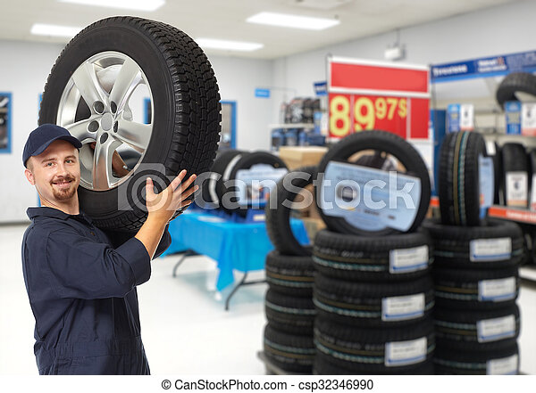 Car mechanic with a tire. - csp32346990