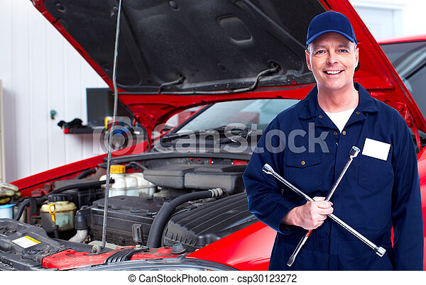 Car mechanic with tire wrench. - csp30123272