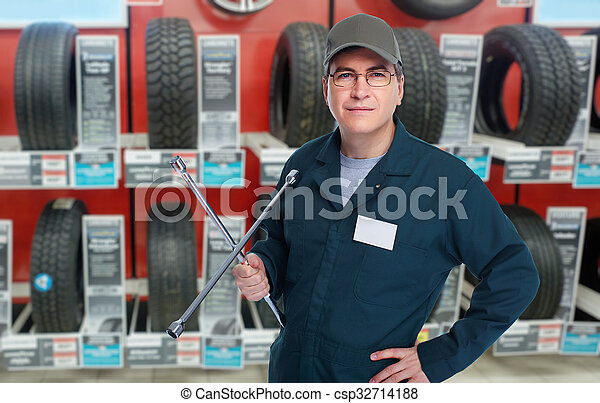 Car mechanic with tire wrench. - csp32714188