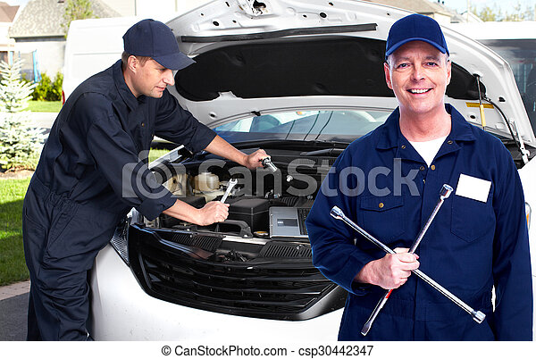 Car mechanic with tire wrench. - csp30442347