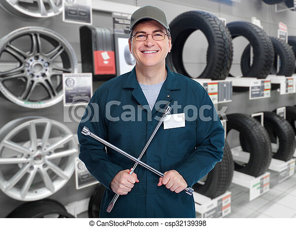 Car mechanic with tire wrench. - csp32139398