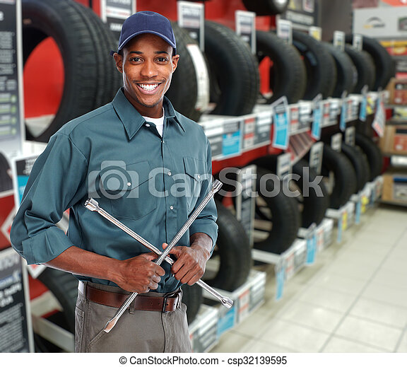 Car mechanic with tire wrench. - csp32139595