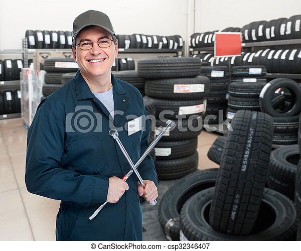 Car mechanic with tire wrench. - csp32346407