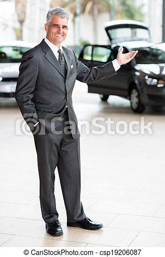 car salesman doing welcoming gesture - csp19206087