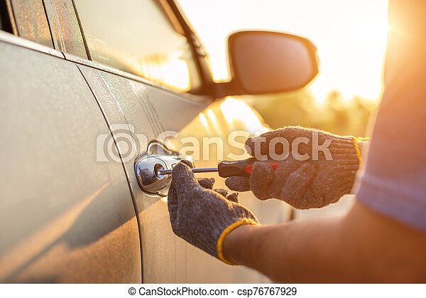 Car technician wearing white gloves and using screwdriver to fix, repair or open the door - csp76767929