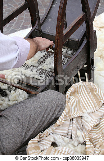 carder while carding with wooden machine to make the mattresses