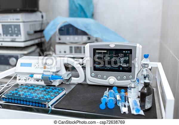Cardiac monitor and syringe at operating table. Pet surgery - csp72638769