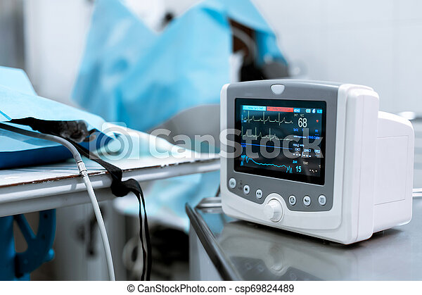 Cardiac monitor at operating table with dog on background. Pet surgery - csp69824489