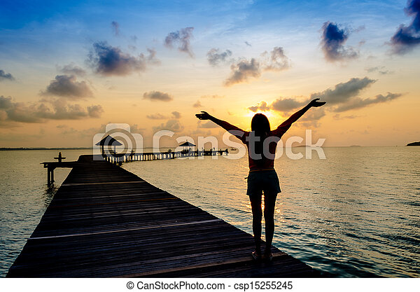 Carefree woman in the sunset on the pier. vacation vitality healthy living concept - csp15255245
