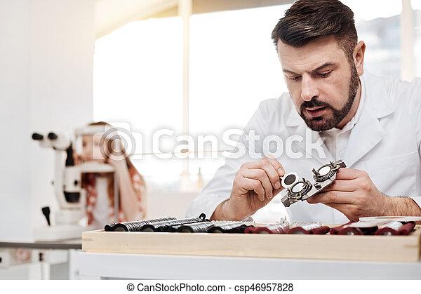 Careful dedicated optician repairing the lenses - csp46957828