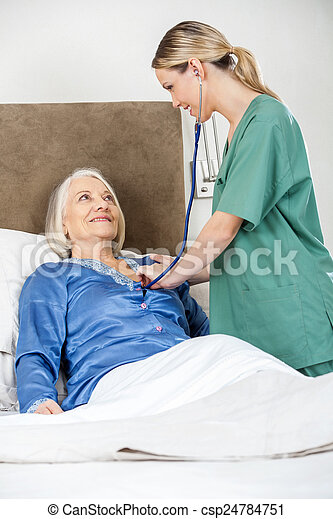 Caregiver Examining Senior Woman With Stethoscope In Bedroom - csp24784751