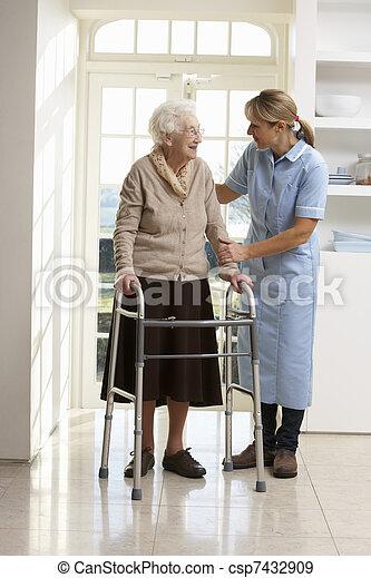 Carer Helping Elderly Senior Woman Using Walking Frame - csp7432909