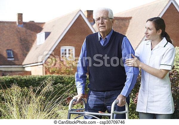 Carer Helping Senior Man To Walk In Garden Using Walking Frame - csp30709746