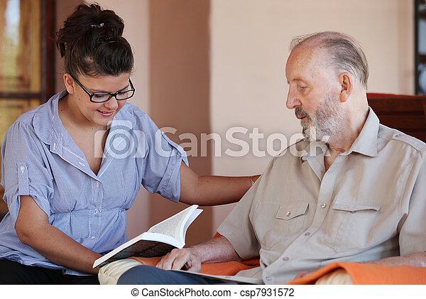 carer reading to senior - csp7931572