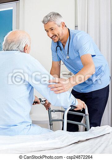 Caretaker Assisting Senior Man To Use Walking Frame - csp24872264