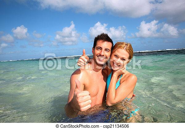 Pareja en una laguna caribeña mostrando pulgares arriba - csp21134506
