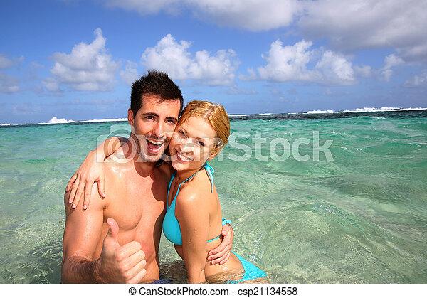 Pareja en una laguna caribeña mostrando pulgares arriba - csp21134558