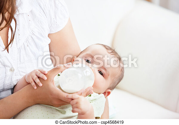 Caring mother feeding her adorable son in the kitchen - csp4568419