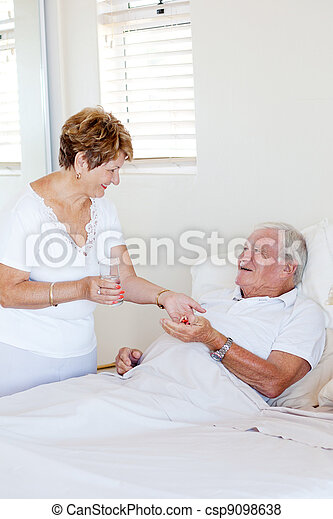 caring senior wife giving medicine to ill husband - csp9098638