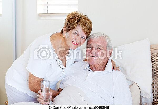 caring senior wife taking care of ill husband - csp9098646