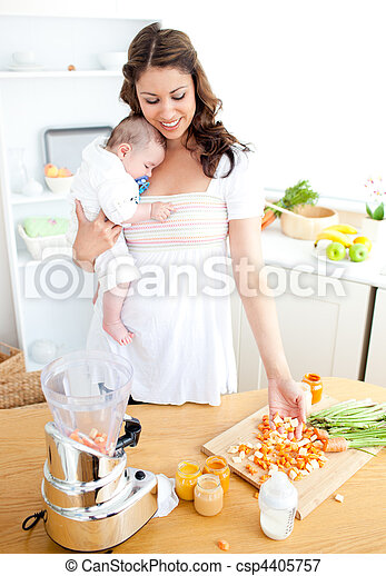 Caring young mother preparing vegetables for her baby in the kitchen at home - csp4405757