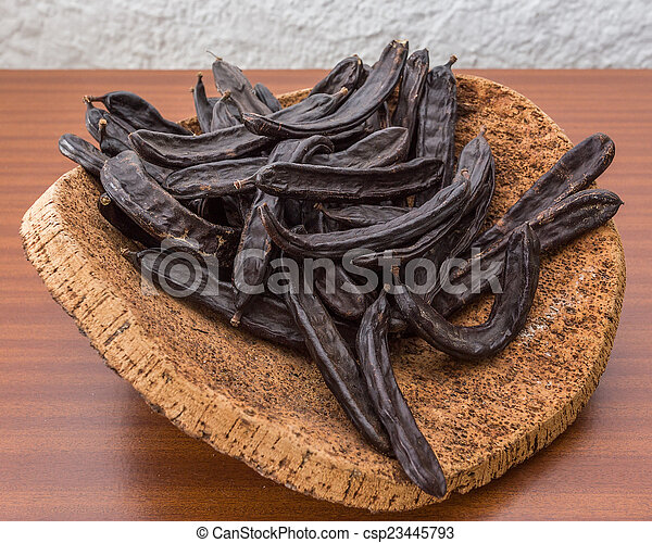Carob pods on cortical stand. On the table. - csp23445793
