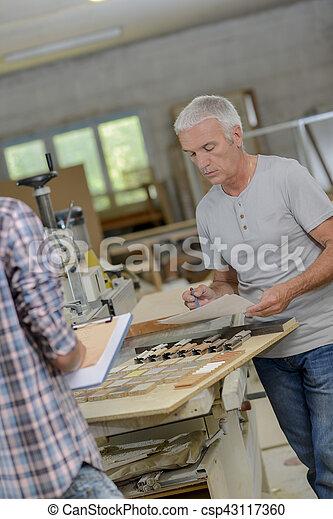 Carpenter and his assistant - csp43117360