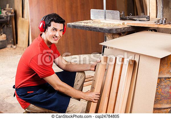 Carpenter Arranging Wooden Planks In Workshop - csp24784805