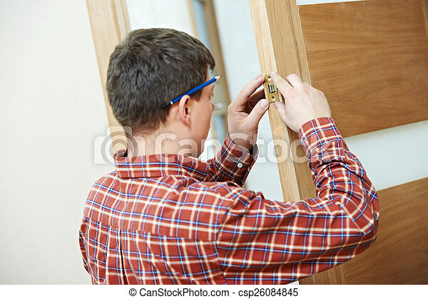 carpenter at door lock installation - csp26084845