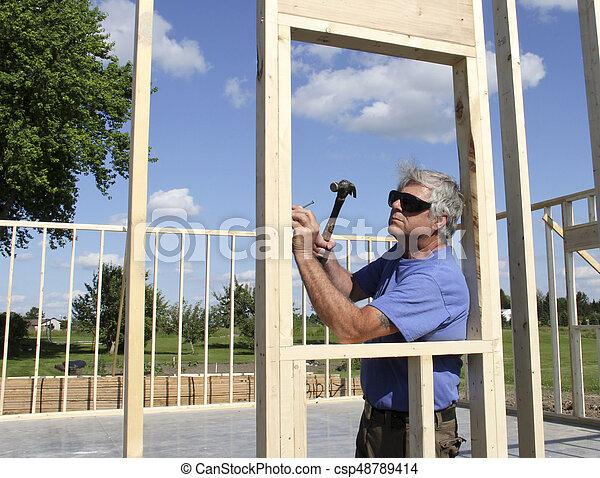Carpenter Building a House - csp48789414