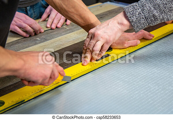 Carpenter doing his job in carpentry workshop. a man in a carpentry workshop measures and cuts laminate - csp58233653