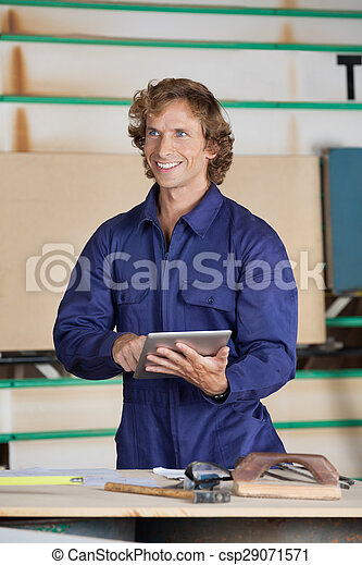 Carpenter Holding Digital Tablet While Looking Away - csp29071571