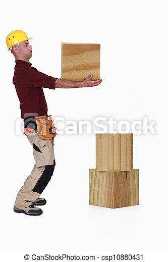 Carpenter lifting heavy block of wood - csp10880431