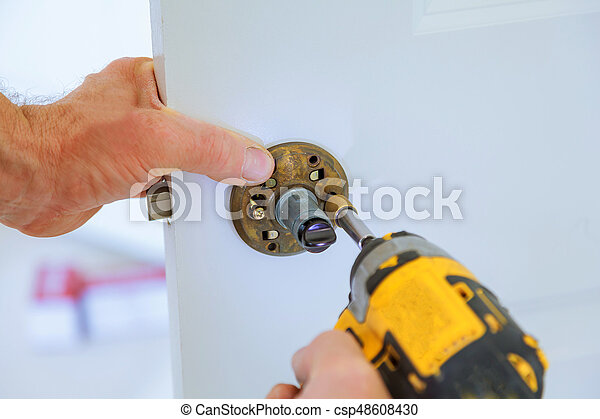 carpenter lock installation with electric drill into interior wood door - csp48608430