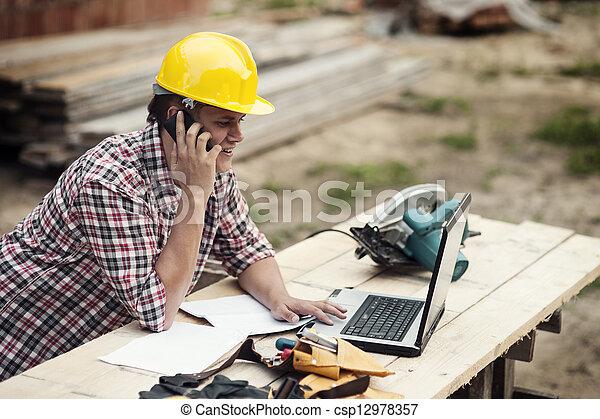 Carpenter talking on mobile phone  - csp12978357
