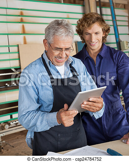 Carpenter Using Digital Tablet With Coworker - csp24784752