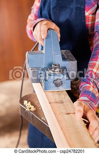 Carpenter Using Electric Planer On Wood - csp24782201
