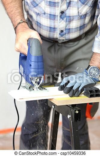 Carpenter using electric saw - csp10459336