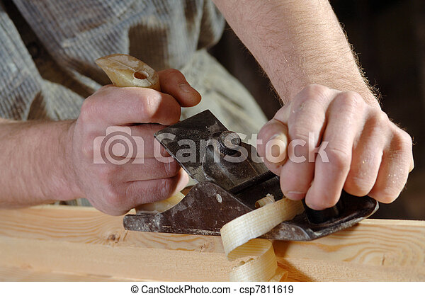 Carpenter working with a planer in his workshop - csp7811619