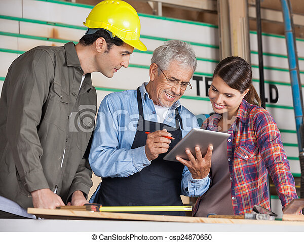 Carpenters Using Tablet Computer In Workshop - csp24870650