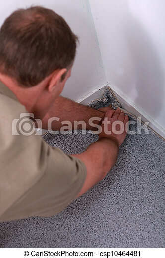Carpet fitter pushing the edges into a corner - csp10464481