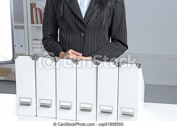 Mujeres de negocios apoyadas en una carpeta en la oficina - csp51808550