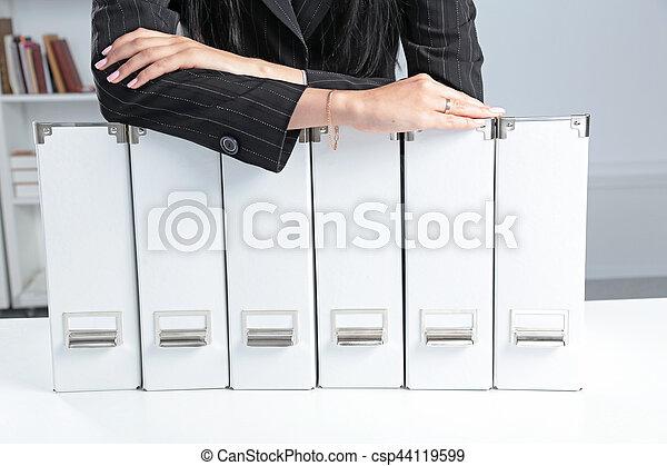 Mujeres de negocios apoyadas en una carpeta en la oficina - csp44119599
