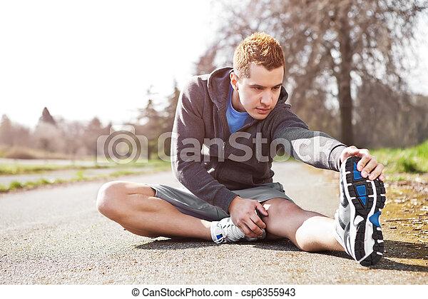 Hombre de raza mixta estirando - csp6355943