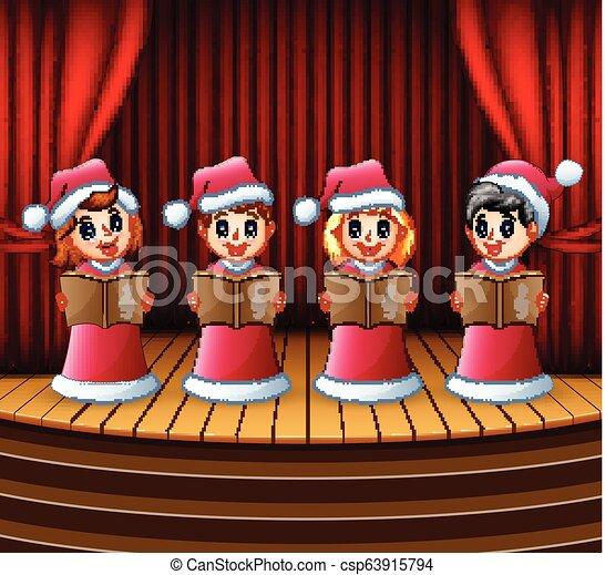 Christmas Carol Singers Figurines.Cartoon Children In Red Santa Costume Singing Christmas Carols On The Stage