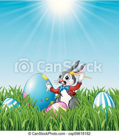 Cartoon Easter bunny painting Easter eggs in the grass - csp59618182