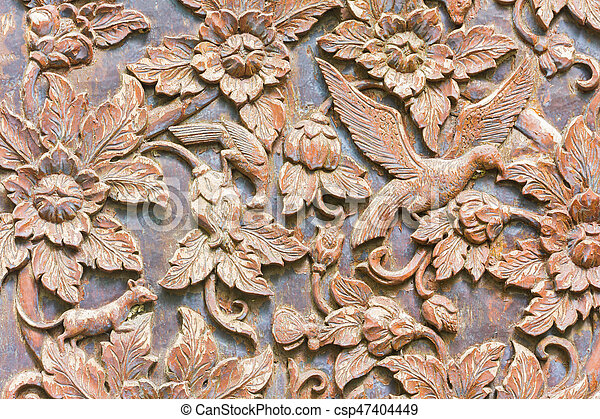 Carved bird and flowers on the wood background, horizontal photo - csp47404449