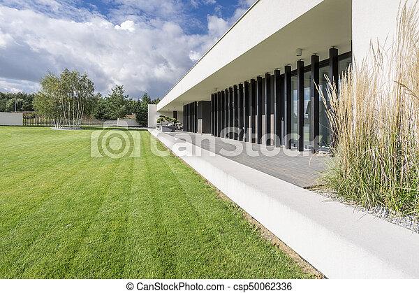 Exterior De Una Casa De Lujo Con Césped Y Terraza