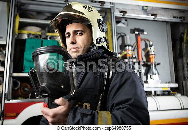 Foto de bombero con casco en el camión de bomberos - csp64980755
